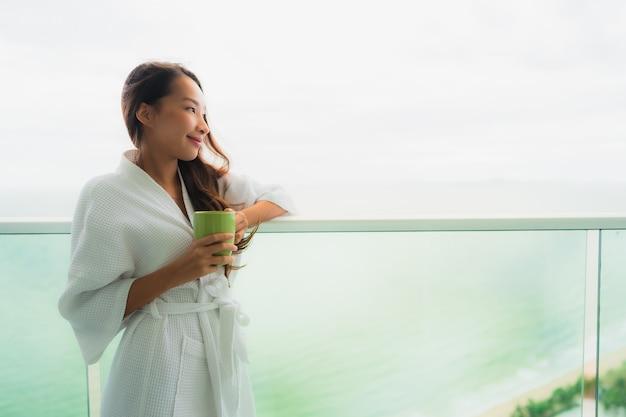 Junge asiatische frauen des schönen porträts, die kaffeetasse balkon am im freien mit seeozeanblick halten Kostenlose Fotos