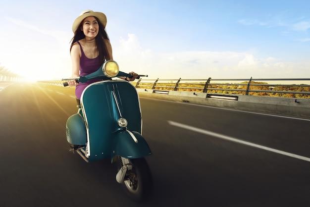 Junge asiatische frauen genießen, einen roller zu reiten und spaß zu haben Premium Fotos