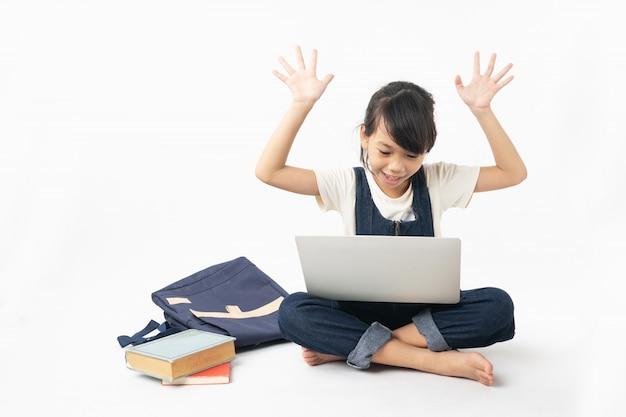 Junge asiatische frohe und glückliche studentin, die auf dem laptop lokalisiert auf weißem hintergrund, internet suchend schaut und erhalten wissen Premium Fotos