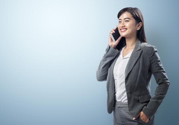 Junge asiatische geschäftsfrau, die auf dem smartphone spricht Premium Fotos