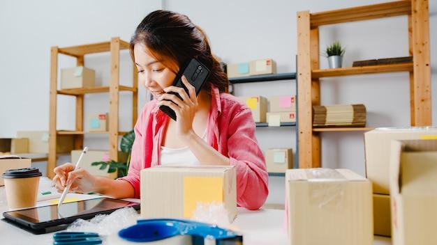 Junge asiatische geschäftsfrau, die handyanruf verwendet, der bestellung empfängt und produkt auf lager überprüft, arbeit zu hause büro. kleinunternehmer, online-marktzustellung, freiberufliches lifestyle-konzept. Kostenlose Fotos