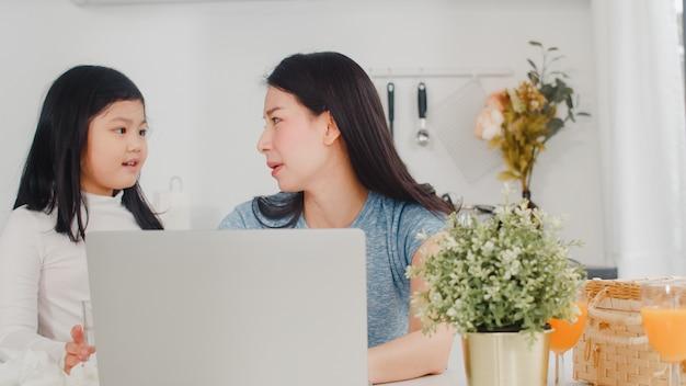 Junge asiatische geschäftsfrau ernst, druck, müde und krank beim an laptop zu hause arbeiten. junge tochter, die ihre mutter tröstet, die morgens schwer in der modernen küche am haus arbeitet. Kostenlose Fotos