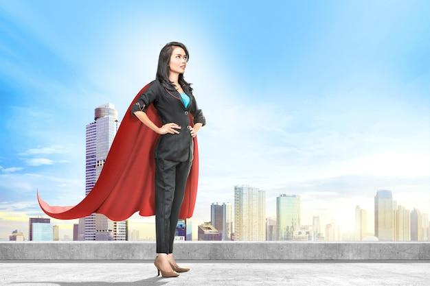 Junge asiatische geschäftsfrau mit dem roten kap, das auf der dachspitze steht Premium Fotos