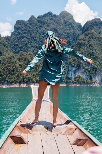 Junge asiatische glückliche frau blogger-tourist in seidenanzug und schal und sonnenbrille im urlaub reisen um thailand auf asiatischem boot, khao sok nationalpark. Kostenlose Fotos