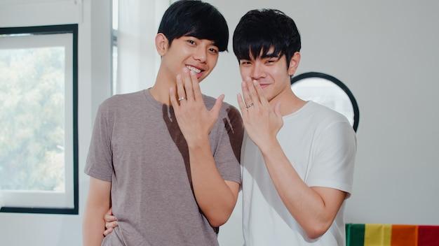 Junge asiatische homosexuelle paare des porträts, die glücklich sind, ring zu hause zeigend. asien lgbtq + männer entspannen sich das toothy lächeln, das zur kamera schaut, während sie im modernen wohnzimmer haus morgens umarmen. Kostenlose Fotos