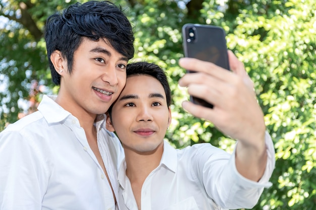 Junge asiatische homosexuelle paare, die selbstporträt mit intelligentem telefon nehmen Premium Fotos