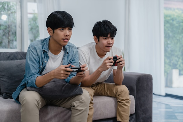 Junge asiatische homosexuelle paare spielen spiele zu hause, jugendlich koreanische lgbtq-männer, die den steuerknüppel hat lustigen glücklichen moment zusammen auf sofa im wohnzimmer am haus verwenden. Kostenlose Fotos