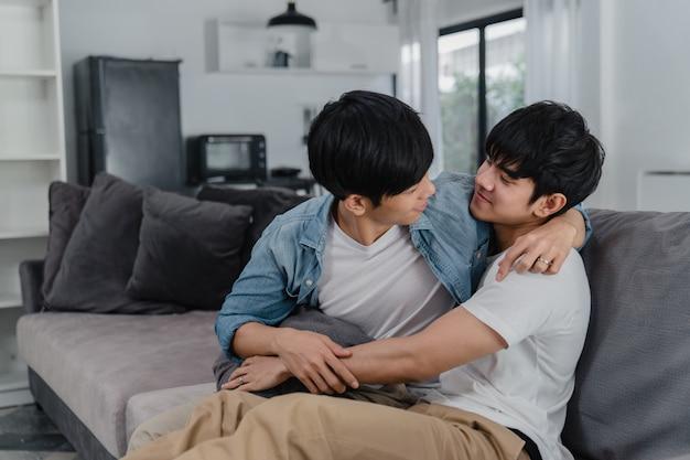 Junge asiatische homosexuelle paare umarmen und küssen zu hause. die attraktiven asiatischen lgbtq-stolzmänner, die glücklich sind, entspannen sich verbringen romantische zeit zusammen beim lügensofa im wohnzimmer. Kostenlose Fotos