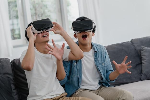 Junge asiatische homosexuelle paare unter verwendung der technologie lustig zu hause, asien-liebhaberkerl lgbtq +, die glücklichem spaß und virtueller realität, vr spielt spiele zusammen beim lügensofa im wohnzimmer zu hause glaubt. Kostenlose Fotos