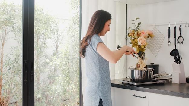 Junge asiatische japanische dame genießen, zu hause zu kochen. lebensstilfrauen glücklich, das lebensmittel zubereitend, das morgens teigwaren und spaghettis zum frühstücksmahlzeit in der modernen küche am haus macht. Kostenlose Fotos