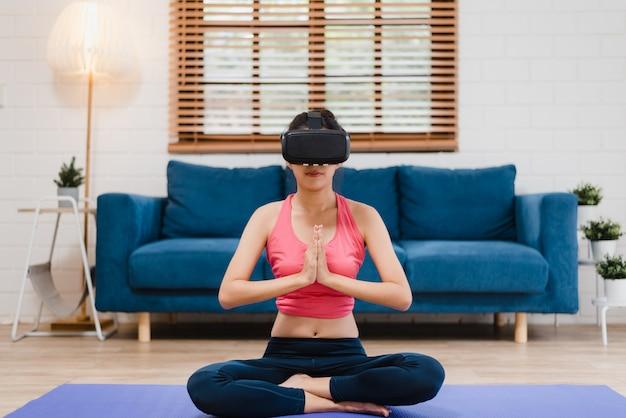 Junge asiatische jugendlichfrau, die simulator der virtuellen realität beim üben von yoga im wohnzimmer verwendet Kostenlose Fotos