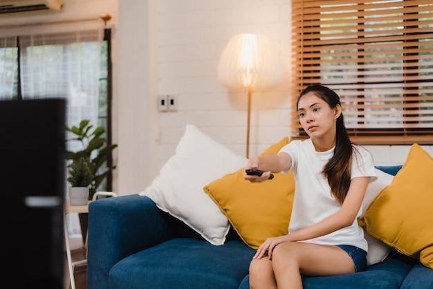 Junge asiatische jugendlichfrau, die zu hause, weibliches glaubendes glückliches lügen auf sofa im wohnzimmer fernsieht. Kostenlose Fotos
