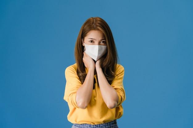 Junge asiatische mädchen tragen medizinische gesichtsmaske, müde von stress und spannung, schaut zuversichtlich auf kamera isoliert auf blauem hintergrund. selbstisolation, soziale distanzierung, quarantäne zur vorbeugung von koronaviren. Kostenlose Fotos