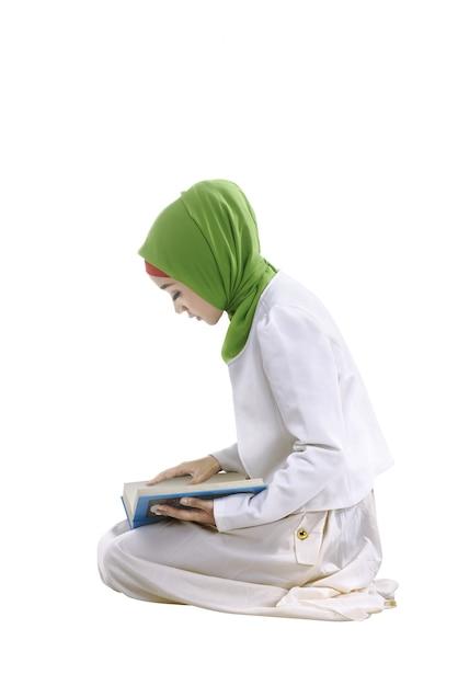 Junge asiatische moslemische frau, die den koran liest Premium Fotos