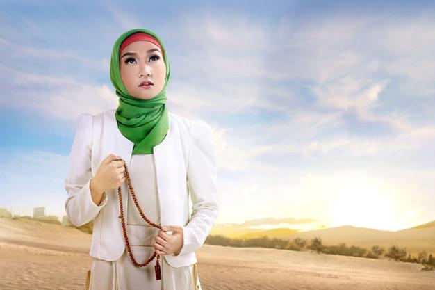 Junge asiatische moslemische frau im schleier, der mit gebetsperlen auf dem sand steht und betet Premium Fotos