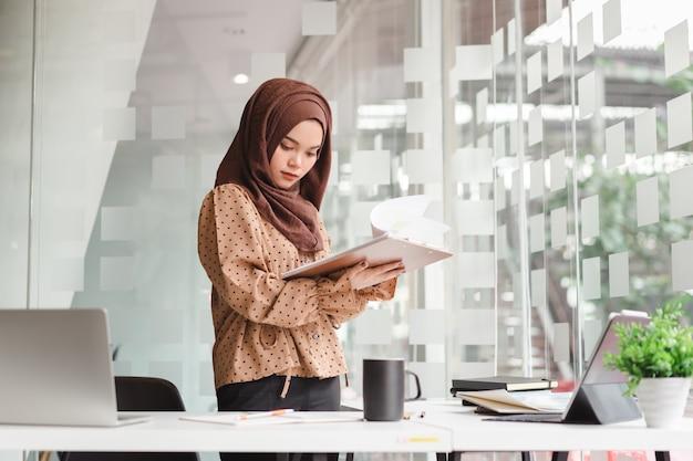 Junge asiatische moslemische geschäftsfrau in der braunen hijab freizeitkleidung geschäft besprechend und bei der stellung im kreativen café lächelnd. Premium Fotos