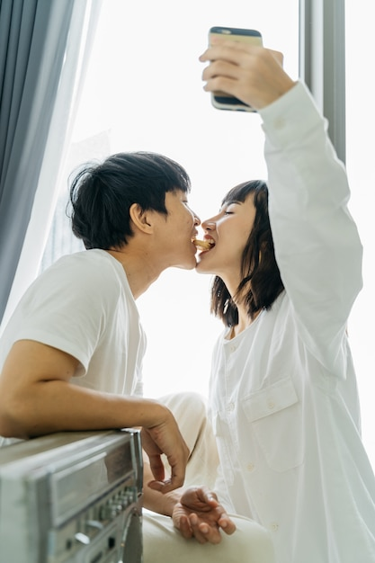 Junge asiatische paare, die ein selfie beim spielen nehmen Premium Fotos