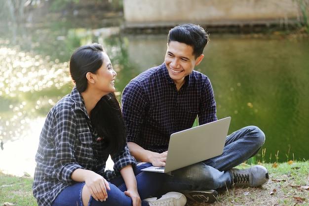 Junge asiatische paare, die spaß mit laptop haben Premium Fotos