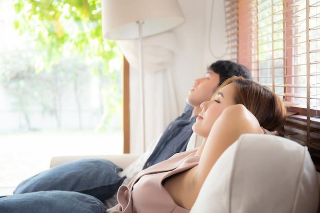 Junge asiatische paare entspannen sich bequem auf sofa Premium Fotos