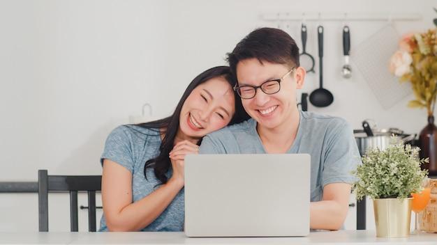 Junge asiatische paare genießen, online auf laptop zu hause zu kaufen. der junge glückliche ehemann und die frau des lebensstils kaufen elektronischen geschäftsverkehr, nachdem sie in der modernen küche am haus morgens gefrühstückt haben. Kostenlose Fotos