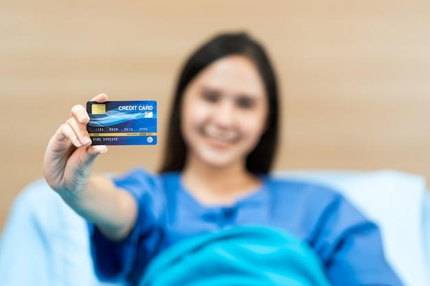 Junge asiatische patientin, die mock-up-gesundheitskreditkarte hält. krankenversicherungskonzept Premium Fotos