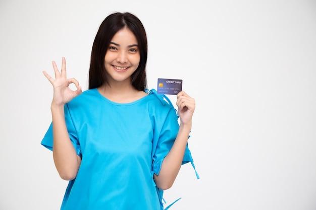 Junge asiatische schöne frau patient zeigt persönliche unfallversicherung kreditkarte und ok zeichen isoliert, pa und health claim services konzept Premium Fotos