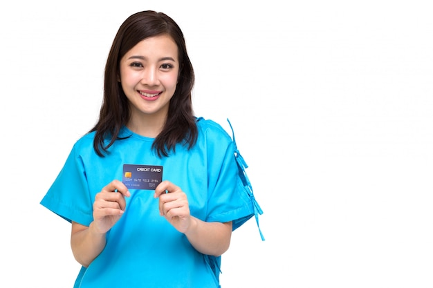 Junge asiatische schöne patientin zeigt kreditkarte isoliert, versicherungspolice durch bankkonzept Premium Fotos