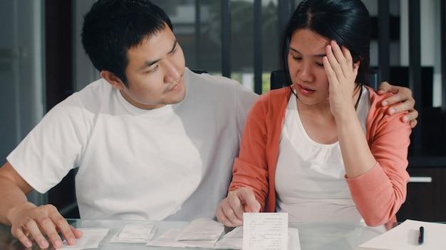 Junge asiatische schwangere paaraufzeichnungen des einkommens und der ausgaben zu hause. mutter besorgt, ernst, stress während rekordbudget, steuern, finanzdokument, das zu hause im wohnzimmer arbeitet. Kostenlose Fotos