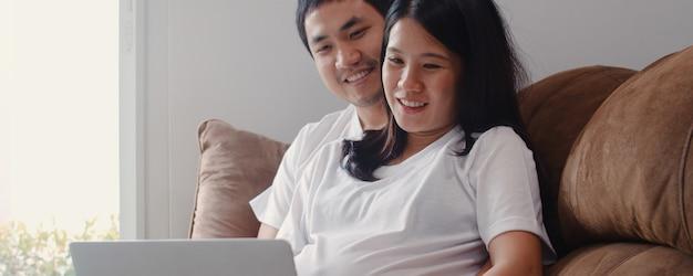 Junge asiatische schwangere paare unter verwendung der laptopsuchschwangerschaftsinformationen. die mutter und vati, die das glückliche lächeln positiv und ruhig sich fühlen, kümmern sich um ihr kind, das zu hause auf sofa im wohnzimmer liegt. Kostenlose Fotos