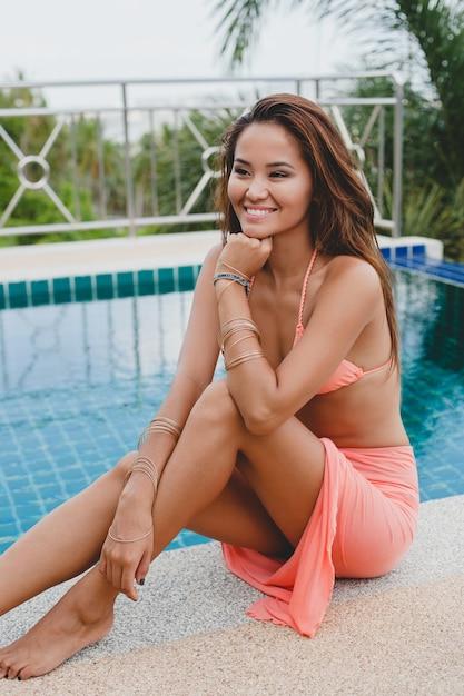 Junge asiatische sexy schöne frau im rosa bikini, am schwimmbad sitzend, schlanke, gebräunte haut, mode-glamour-accessoires, armbänder, entspannt, lächelnd, sinnlich, sommerferien Kostenlose Fotos
