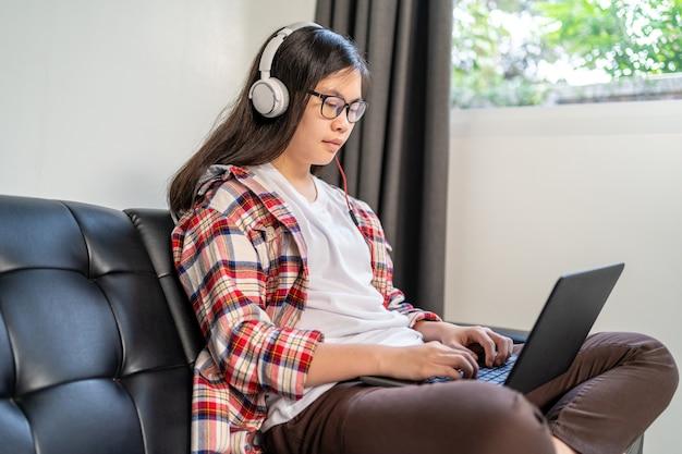 Junge asiatische studentin, die von zu hause aus während der sperrung der stadt aufgrund der ausbreitung des koronavirus arbeitet und studiert Premium Fotos
