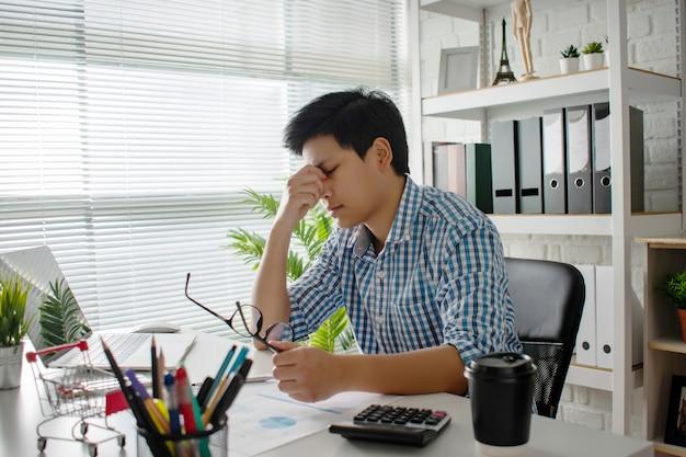 Junge asiatische unternehmen haben kopfschmerzen und sind bei der arbeit krank Premium Fotos