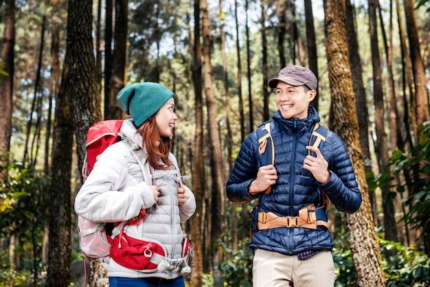Junge asiatische wandererpaare mit dem rucksack, der steht und sich schaut Premium Fotos