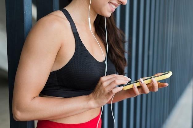 Junge athletenfrau mit einem smartphone Kostenlose Fotos