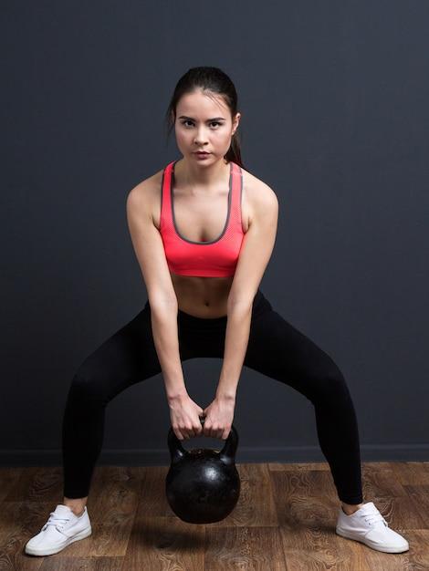 Junge athletische frau, die hocken mit gewichten tut Premium Fotos