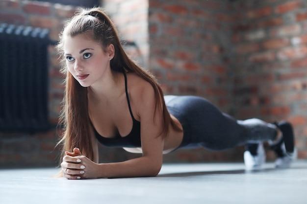 Junge athletische frau, die ihre übungsroutine zu hause tut Kostenlose Fotos