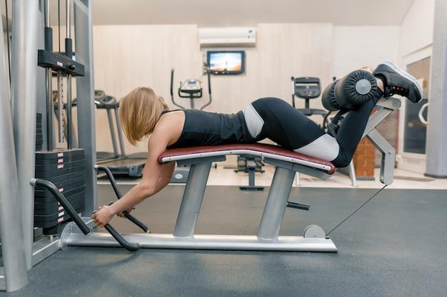 Junge athletische frau, die übungen auf beinen und hinterteilen in der turnhalle tut Premium Fotos
