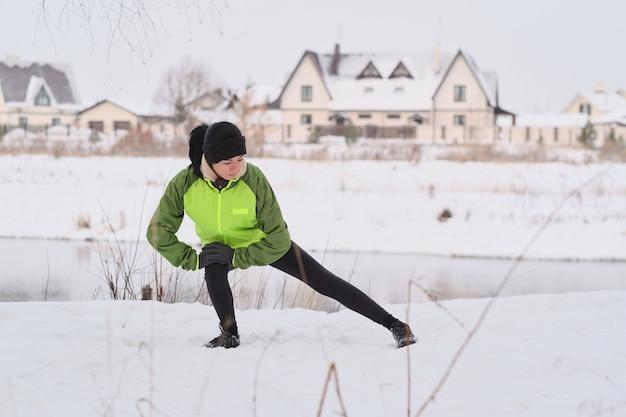 Junge athletische frau im warmen stirnband, das sich auf knie stützt und bein streckt, während im winter aufwärmen tut Premium Fotos