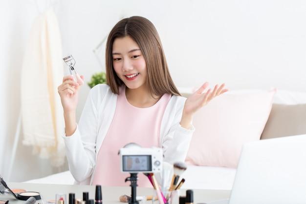 Junge attraktive asiatische frau schönheit vlogger hält wimpernzange, die live-streaming vor der kamera tut Premium Fotos