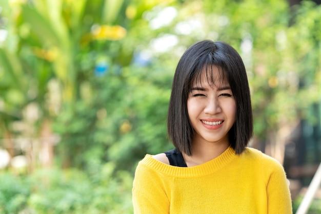 Junge attraktive asiatische kreative designerfrauenstellung, lächeln, die kamera betrachtend, die glücklich sich fühlt. Premium Fotos
