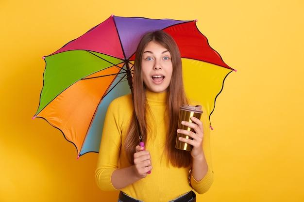 Junge attraktive dame mit erstauntem gesichtsausdruck, der mit buntem regenschirm und kaffee zum mitnehmen aufwirft, steht mit geöffnetem mund Kostenlose Fotos