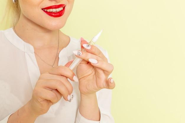 Junge attraktive frau der vorderansicht im weißen hemd, das mit ihren nägeln auf der grünen oberfläche arbeitet Kostenlose Fotos