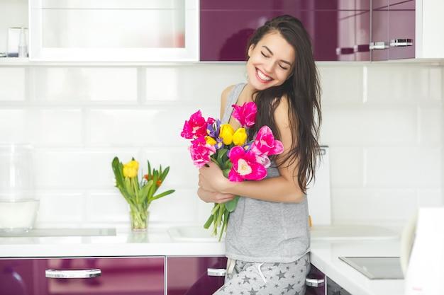 Junge attraktive frau, die blumen hält. dame in der küche mit tulpen. hausfrau morgens, die auf der hauptküche steht. Premium Fotos