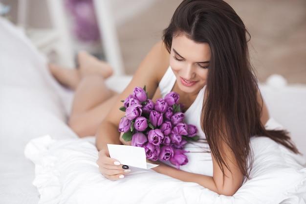 Junge attraktive frau, die blumen hält. schöne frau mit tulpen auf dem bett liegend Premium Fotos