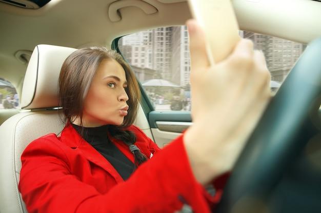 Junge attraktive frau, die ein auto fährt Kostenlose Fotos