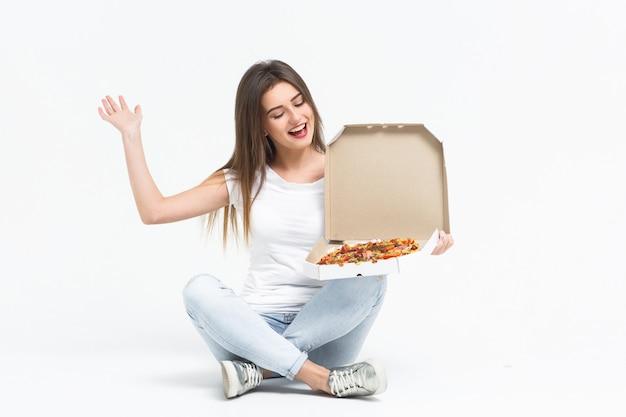 Junge attraktive frau, die ein stück köstliche pizza isst. sie trägt ein t-shirt, jeans und turnschuhe, die zu hause auf dem boden liegen. lebensmittellieferservice. Premium Fotos