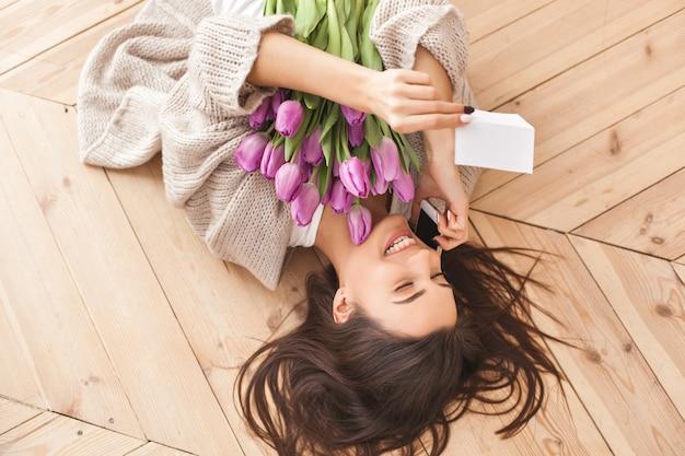 Junge attraktive frau, die einen blumenstrauß von blumen hält Premium Fotos