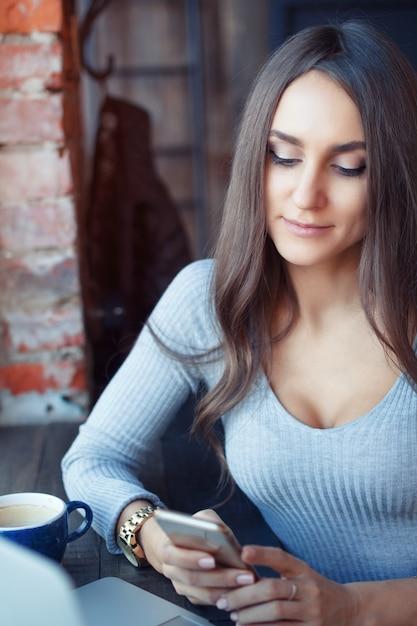 Junge attraktive frau, die in einem café arbeitet und kaffee trinkt Premium Fotos