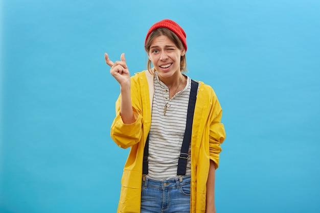 Junge attraktive frau, die roten hut, gelbe jacke und jeansoverall trägt, zeigt etwas sehr wenig mit den händen beim gestikulieren. fischerin, die die größe des fisches demonstriert Kostenlose Fotos