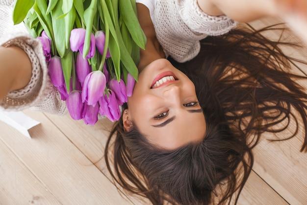 Junge attraktive frau, die zuhause selfie mit blumen macht Premium Fotos